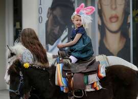 Five year old Ava-Grace Bender got her ears blown around as she rode one of the miniature horses from Victoria's Fashion stables Sunday April 5, 2015. The 24th annual Union Street Easter parade and spring celebration had something for everyone including a little rain in San Francisco, Calif.