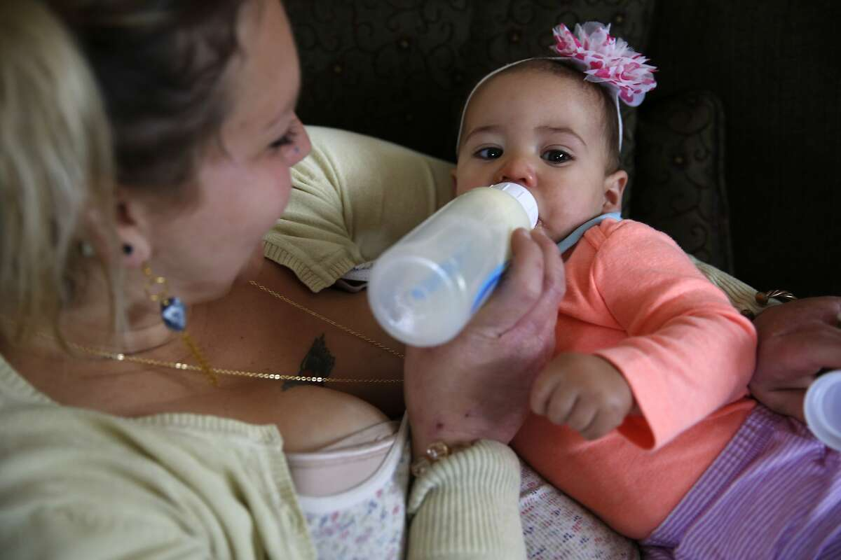 Sam Torreano feeds private donor breast milk to her 8-month-old baby Seneca Jahi in Oakland, Calif., on Sunday, April 5, 2015.