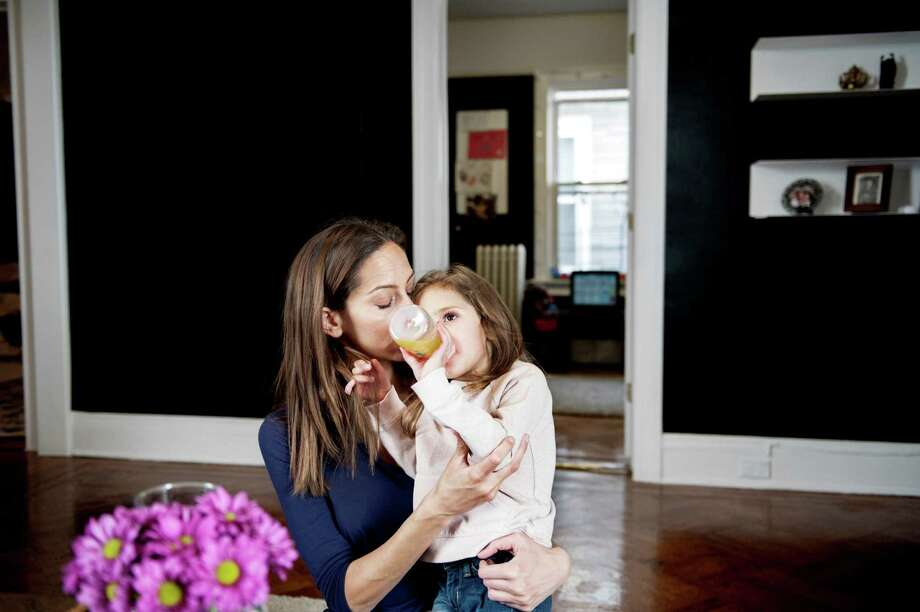 """Christine Salerno holds her daughter, Lily, 4, at home in the Brooklyn borough of New York, March 22, 2015. A rare neurological disorder has mildly hampered Lily's development, and Salerno has learned how overwhelming it can be to financially plan for special needs children. """"She has 10 therapists and 15 doctors, and I manage all of this,"""" Salerno said. (Emily Andrews/The New York Times) Photo: EMILY ANDREWS, STR / New York Times / NYTNS"""