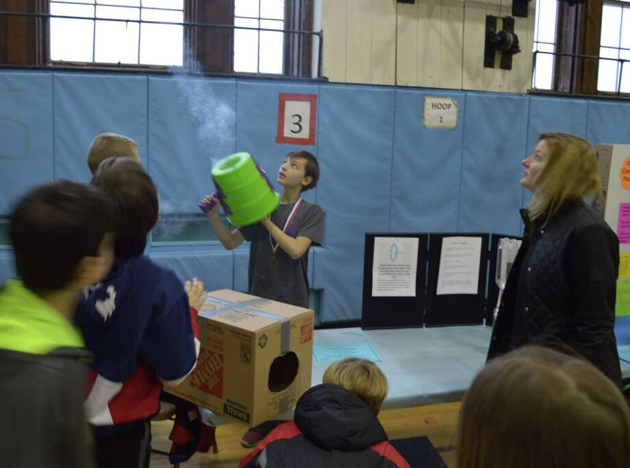 Students turned into teachers March 26 at East Greenbush's Genet Elementary School STEM Learning Fair. They conducted research on topics such as density, monorails and vortexes and demonstrated their findings to parents, teachers and community members in the school gymnasium. Here, fifth-grader Carter Durivage explained vortexes by showing colored liquids swirling in connected two-liter bottles and by shooting fog out of two different instruments. (Mark Adam)
