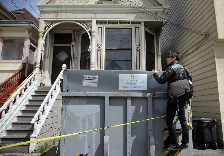 San Francisco Supervisor Eric Mar tries to look into a dumpster as he checked in with neighbors on Sunday, April 5, 2015 at the home in San Francisco , Calif. where a mummified body had been discovered the day before. Mar was looking for comments from neighbors on how the city could prevent the spread of vermin and spiders as the home is emptied and to provide services for mental health or senior care to stop such a thing from happening to other elders. Photo: Carlos Avila Gonzalez, The Chronicle