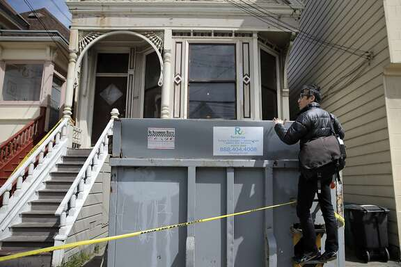 San Francisco Supervisor Eric Mar tries to look into a dumpster as he checked in with neighbors on Sunday, April 5, 2015 at the home in San Francisco , Calif. where a mummified body had been discovered the day before. Mar was looking for comments from neighbors on how the city could prevent the spread of vermin and spiders as the home is emptied and to provide services for mental health or senior care to stop such a thing from happening to other elders.