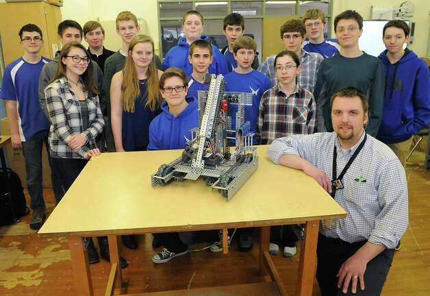 Members of the Blue Streaks Robotics Club including Preston Sweeney, middle school technology teacher and club advisor, lower right, pose with their robot during a meeting at Saratoga Springs High School on Tuesday, March 31, 2015 in Saratoga Springs, N.Y. The Blue Streaks Robotics Club won the NYS Championship in February at Onondaga Community College. They're going to nationals next month to take on 450 teams from across the world. (Lori Van Buren / Times Union) Photo: Lori Van Buren / 00031241A