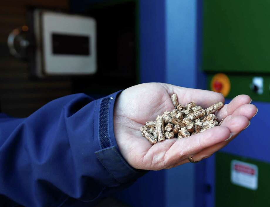 In this Wednesday, April 1, 2015 photo, Eric Besenfelder, director of facilities for the Coxsackie-Athens Central Schools, holds hardwood pellets used in a wood burning boiler at Athens Elementary School in Athens, N.Y.  Financial incentives and technological advances have led a growing number of schools, local government buildings, nature centers and homes to switch from fossil fuels to renewable heat in northern states. (AP Photo/Mike Groll)  ORG XMIT: NYMG202 Photo: Mike Groll / AP