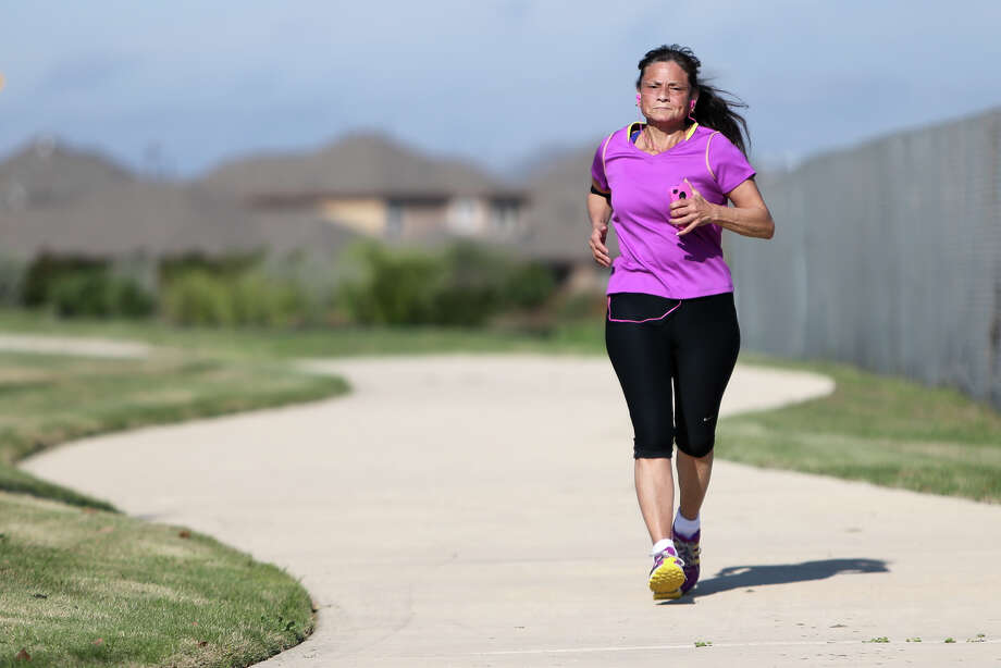 Yvonne Martinez on a morning run near her home on Wednesday, March 25, 2015. Martinez credits runing for helping her stay cancer free. Photo: Marvin Pfeiffer /San Antonio Express-News / Express-News 2015