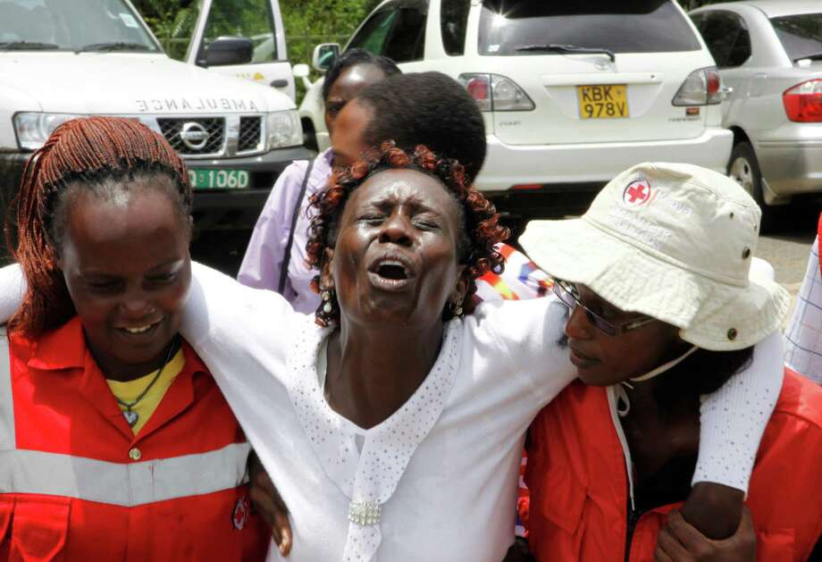 Red Cross staff console a woman after she viewed the body of a relative killed in Thursday's attack on a university, at Chiromo funeral home, Nairobi, Kenya, Sunday, April 5, 2015. Al-Shabab gunmen rampaged through a university in northeastern Kenya at dawn Thursday, killing scores of people in the group's deadliest attack in the East African country. (AP Photo/Khalil Senosi) ORG XMIT: XKS101 Photo: Khalil Senosi / AP