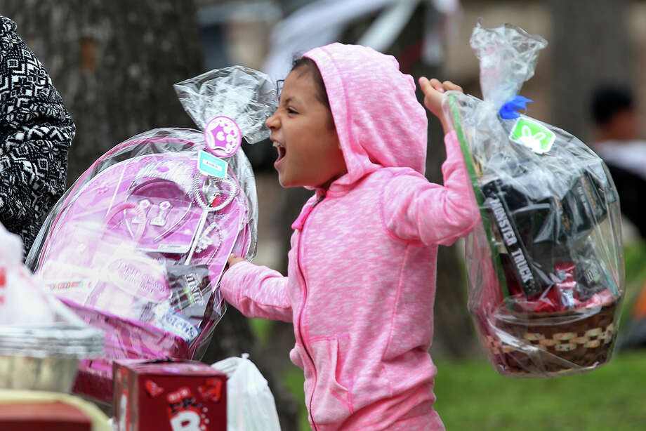 Eliana Villarreal, 7, gets a hold of the baskets while celebrating Easter at Brackenridge Park, Sunday, April 5, 2015. The park attracts thousands during the Holiday. Many have been using the park during Easter for generations. Photo: JERRY LARA, San Antonio Express-News / © 2015 San Antonio Express-News