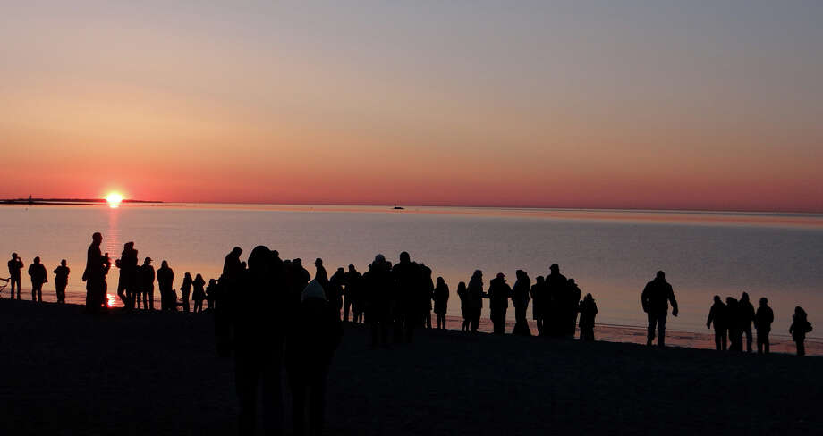 Dawn breakls over Jennings Beach early Sunday at a crowd celebrates Easter at a sunrise service organized by First Church Congregational. Photo: Mike Lauterborn / Fairfield Citizen