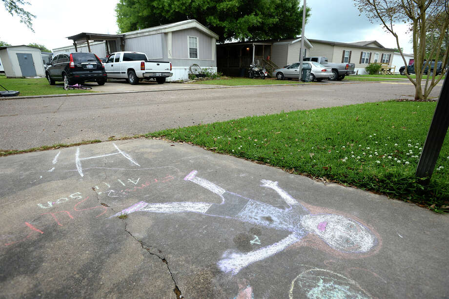 Sidewalk chalk covers the driveway of a Nederland home  located a short distance from the Al Price Unit. The topic of moving sex offenders into the unit will be discussed in Monday's Commissioners' meeting.  Photo taken Friday, April 03, 2015  Guiseppe Barranco/The Enterprise Photo: Guiseppe Barranco, Photo Editor