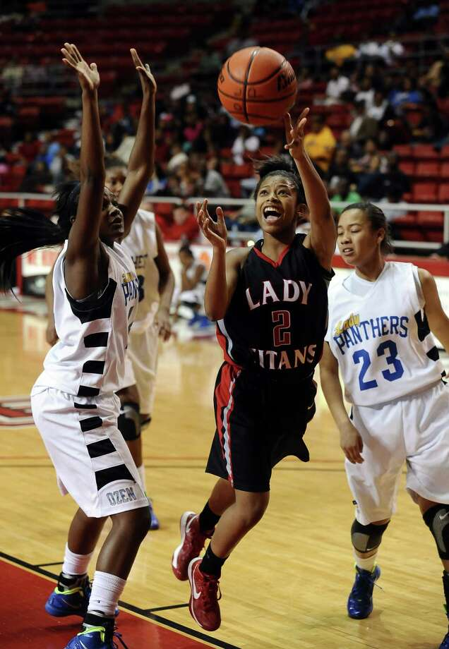 Lady Titan Joyce Kennerson, #2, drives between three Lady Panthers go lock-in 2 points during the Port Arthur-Memorial Lady Titans high school basketball game against the Ozen Lady Panthers on Saturday December 1, 2012, in the championship basketball game of the annual BISD YMBL South Texas Shootout at the Lamar University Montagne Center. Port Arthur-Memorial won over Ozen 53-52. Photo taken: Randy Edwards/The Enterprise Photo: Randy Edwards