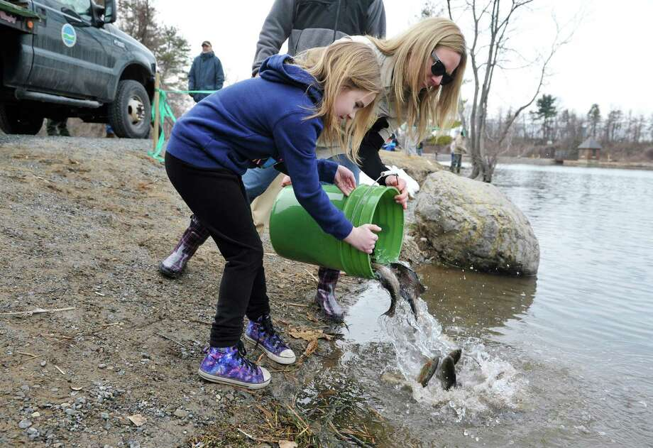 Makenna Seyler, left, 9, from Guilderland and Joelle Ernst, a fishing promotions biologist with the DEC dump a bucket of rainbow trout into the water during a free fishing event at Rensselaer Lake on Monday, April 6, 2015, in Albany, N.Y.  The lake was stocked by the DEC with 2,000 rainbow trout.  The DEC will have staff members at Rensselaer Lake this week through Friday from 10:00am to 2:00pm each day to provide fishing assistance to children and adults.   (Paul Buckowski / Times Union) Photo: PAUL BUCKOWSKI / 00031311A