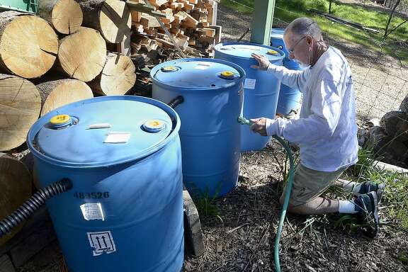 FILE - In this March 13, 2015 file photo, Tom Boswell demonstrates how his new rain recovery system works at collecting rainwater from his roof into 50-gallon drums, then used to water landscaping in Shaver Springs, Calif. On Wednesday, April 1, 2015, California Gov. Jerry Brown ordered the first mandatory, statewide water cutbacks by cities and towns as the state's nearly 40 million people head into a fourth summer of severe drought. Under the order the state can fine water agencies $10,000 a day if they fail to meet state targets for water conservation.