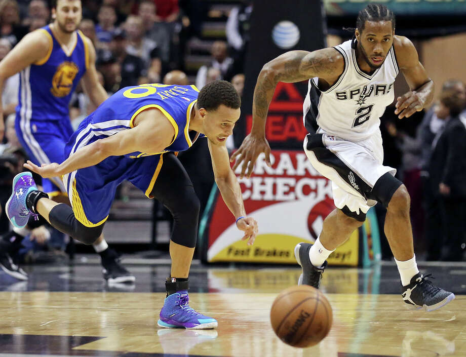 Golden State Warriors' Stephen Curry and Spurs' Kawhi Leonard chase after a loose ball during first half action on April 5, 2015 at the AT&T Center. Photo: Edward A. Ornelas /San Antonio Express-News / © 2015 San Antonio Express-News