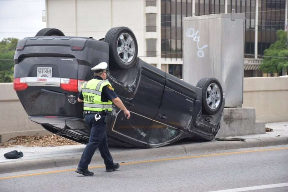 A woman driving an SUV in the westbound lanes of the Loop 410 access road was involved in a rollover crash with another vehicle around 1:30 p.m. on April 6, 2015. Photo: Mark D. Wilson/San Antonio Express-News