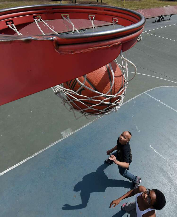 Shamel Wright, 9, left, and Quavair Banks, 12, watch as the ball goes through the hoop at the Madison Avenue playground on the corner of Ontario Street Monday afternoon, April 6, 2015, in Albany, N.Y.   (Skip Dickstein/Times Union) Photo: SKIP DICKSTEIN