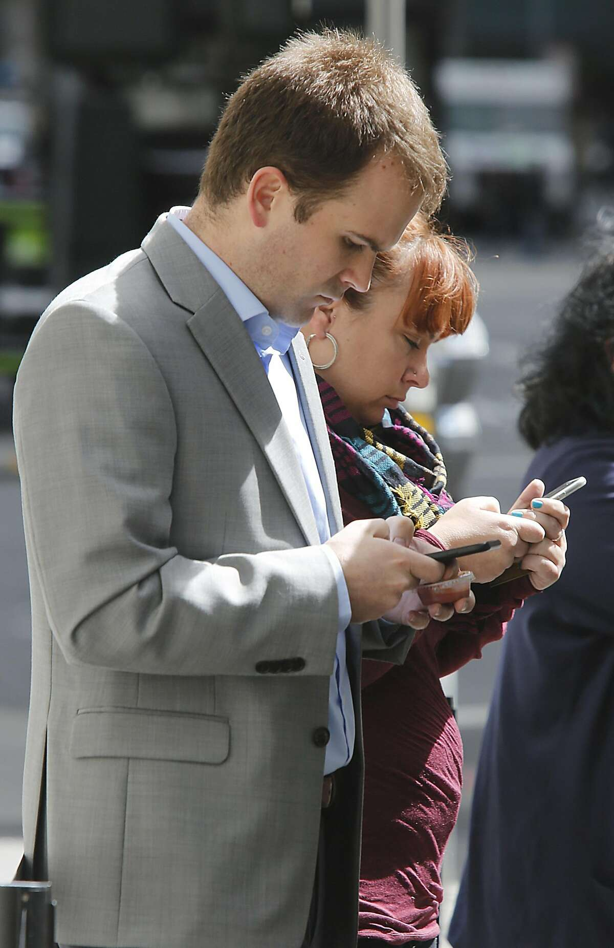 Joe Cagajeski (front) and Erica Vaughn (behind) on their phones while they wait for food from the Senior Sisig food truck in the financial district in San Francisco, California, on Monday, April 6, 2015.