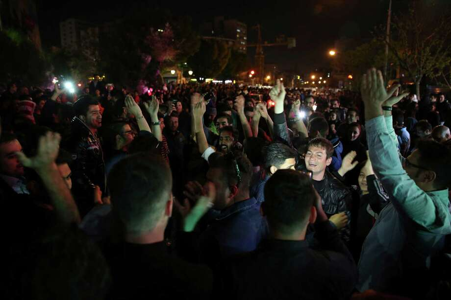 Iranians celebrate a framework agreement on Iran's nuclear program between their country and six world powers, in a street in Tehran, Iran, Friday, April 3, 2015. For the second consecutive night in Tehran, hundreds of Iranians celebrated the deal in major streets and squares. Carrying flags of Iran, singing and dancing, many chanted in support to President Hassan Rouhani and Foreign Minister Mohammad Javad Zarif. (AP Photo/Vahid Salemi) Photo: Vahid Salemi / Associated Press / AP