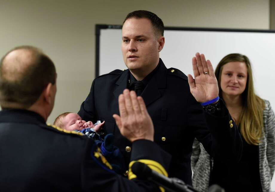 Officer Mike Colwell, center,  is sworn in at his new rank of sergeant by Troy Police Chief John Tedesco, left, as he holds his infant son Andrew while wife Julie looks on Monday morning, April 6, 2015, in the City Council Chambers in Troy, N.Y. (Skip Dickstein/Times Union) Photo: SKIP DICKSTEIN / 00031315A