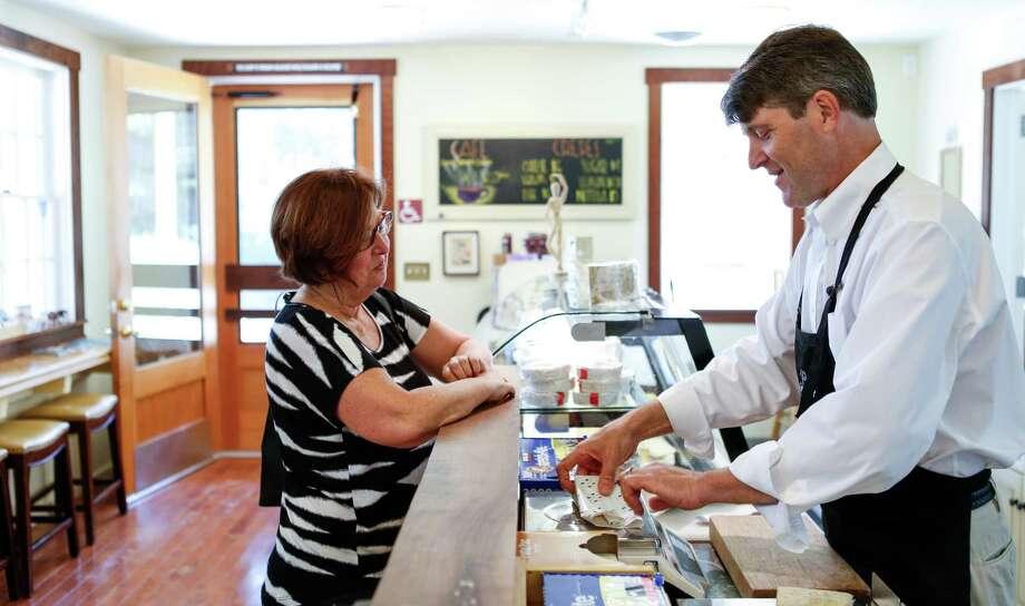 Omar Mueller, owner of Freestone Artisan Cheese, chats with customer Julie Davis of Sebastopol on Thursday, April 2, 2015 in Sebastopol, Calif. Photo: Russell Yip / The Chronicle / ONLINE_YES
