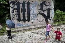 Integrantes masculinos novatos de la MS13 tienen que atravesar un proceso de iniciación en el que son golpeados por otros miembros mientras uno de ellos cuenta hasta 13 en voz alta. Una familia camina en 2014 por un lugar donde hay un símbolo en la pared de Mara Salvatrucha en Ilopango, El Salvador