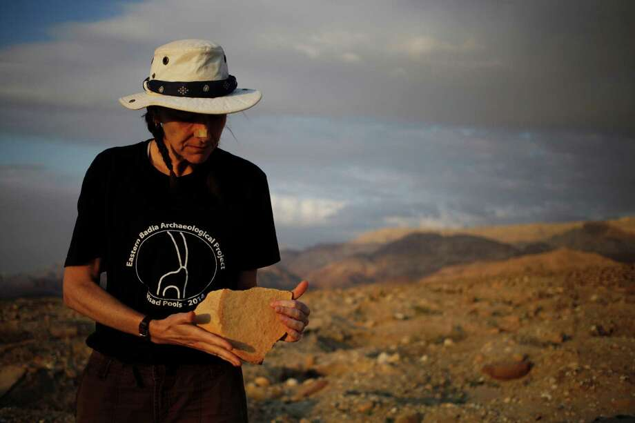 """In this photo taken Thursday, March 19, 2015, archaeologist Morag Kersel holds a pottery shard found at a Bronze Age cemetery, known as Fifa, in southern Jordan. Kersel heads a program called """"Follow The Pots"""" that, based on aerial photography and conversations with looters, tries to track stolen artifacts to middlemen, dealers and customers. (AP Photo/Sam McNeil) Photo: Sam McNeil, STF / Associated Press / AP"""