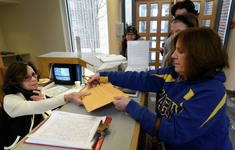 Robin Jira, right, delivers letters to the Albany Diocese receptionist addressed to Albany Bishop Edward Sharfenberger from parents upset by the plan to move students from the Bishop Maginn School to another location Monday morning, April 6, 2015, in Albany, N.Y.   (Skip Dickstein/Times Union) Photo: SKIP DICKSTEIN / 00031310A