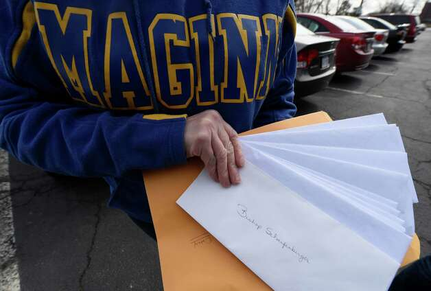 Robin Jira holds letters to be delivered to Albany Bishop Edward Sharfenberger from parents upset by the plan to move students from the Bishop Maginn School to another location Monday morning, April 6, 2015, in Albany, N.Y.   (Skip Dickstein/Times Union) Photo: SKIP DICKSTEIN / 00031310A