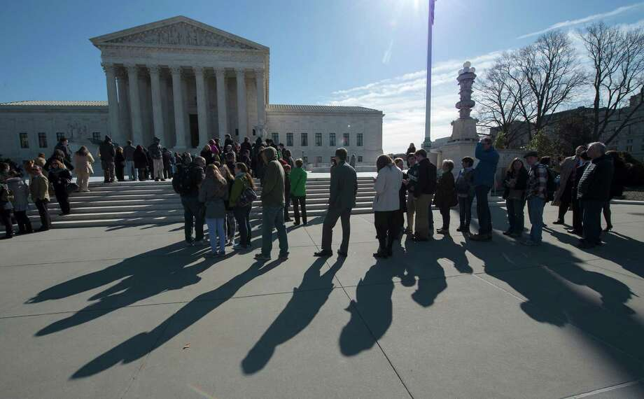 In this photo taken March 23, 2015, people wait outside the Supreme Court in Washington in hopes to gain admittance for oral arguments. Protesters who demonstrated inside the U.S. Supreme Court are facing the threat of a year in jail and stiff fines, a sign that prosecutors and the justices themselves are losing patience over the courtroom interruptions after the third protest in just over a year. Five people arrested last week after voicing displeasure with court decisions that removed limits on political campaign contributions now face charges including one that carries a maximum jail term of a year and up to a $100,000 fine _ a sharp escalation from the possible penalties sought after two earlier protests. (AP Photo/Molly Riley) ORG XMIT: WX101 Photo: Molly Riley / FR170882 AP