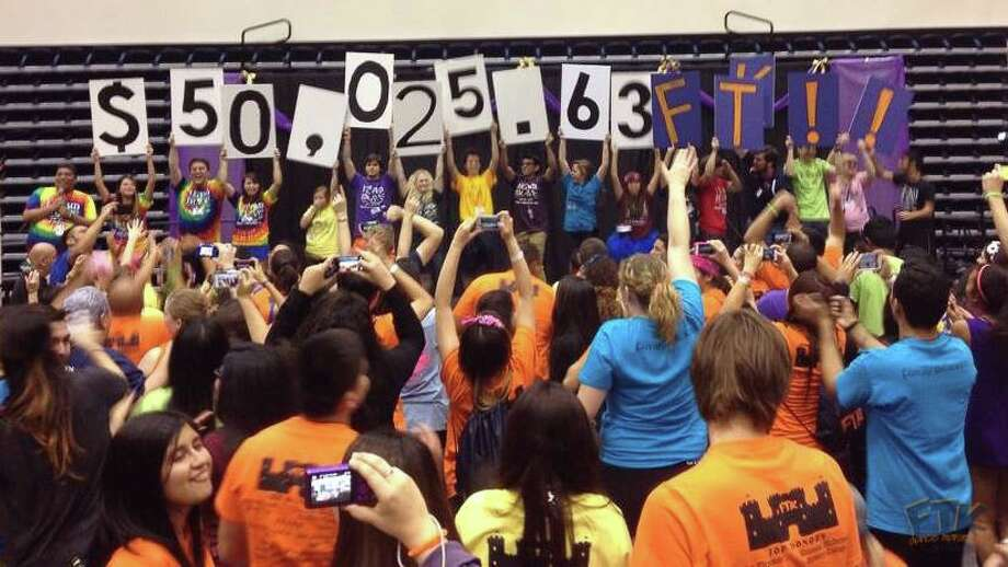 Participants hold up the tally of funds raised at a dance marathon sponsored by For The Kids, a University of Texas at San Antonio student group that helps children with cancer and their families. Photo: Courtesy Of For The Kids / Courtesy Of For The Kids