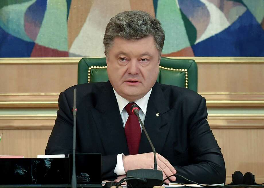 Ukraine's President Petro Poroshenko speaks to official in his office in Kiev, Ukraine, Monday, April 6, 2015.  Poroshenko on Monday April 6, 2015, publicly lifted his objections to a referendum that could give more powers to the restive regions engulfed in more than a year of warfare, reversing his government's previous position. (AP Photo/Mykola Lazarenko, Pool) ORG XMIT: XEL101 Photo: Mykola Lazarenko / Presidential Press Service