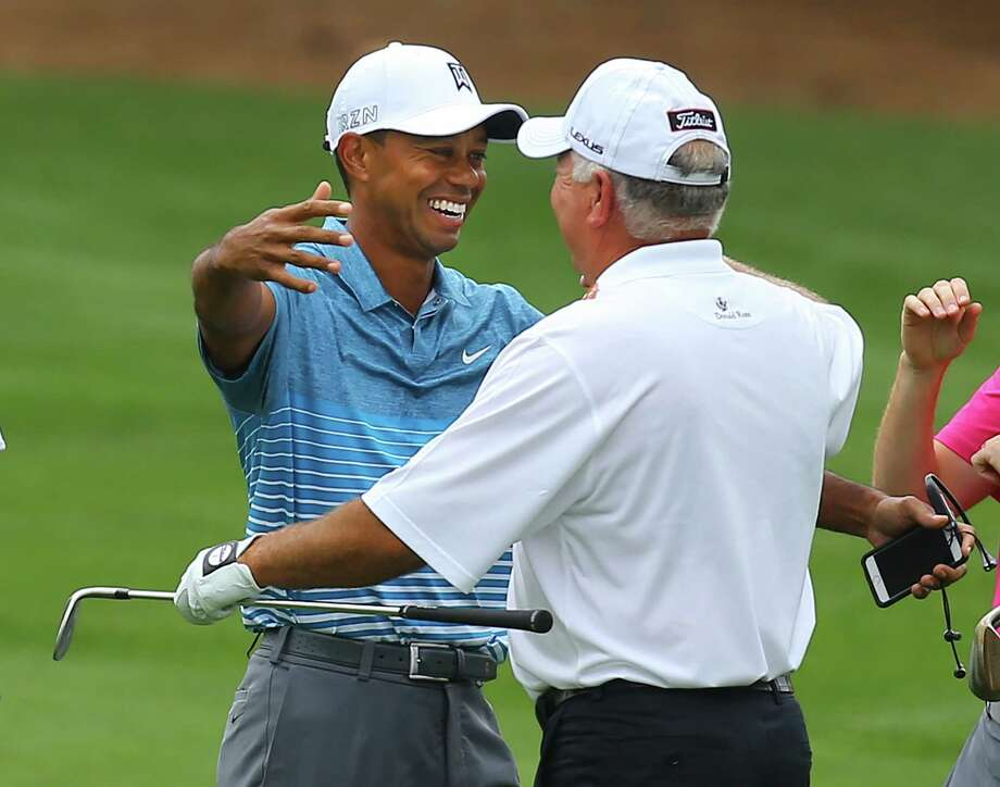 Tiger Woods greets Mark O'Meara before they embark on a much-scrutinized partial round Monday at Augusta. Photo: Curtis Compton, MBR / Atlanta Journal-Constitution