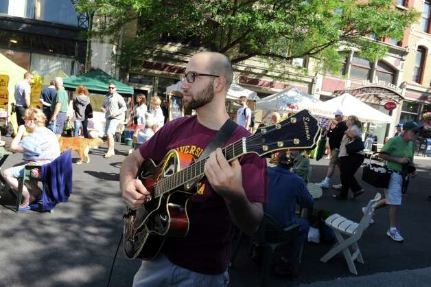 Zac Cohen plays guitar with the C.C. Vagabonds last summer at the Troy Farmers Market, which brings big crowds to the city. (Michael P. Farrell/Times Union) Photo: Michael P. Farrell / 00027640A