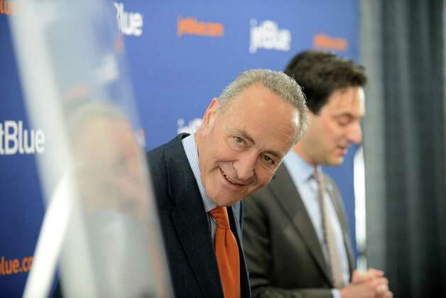Sen. Charles Schumer, left, looks over route map as Jeffrey Goodell, vice president government affairs for JetBlue, right, announces the start the of JetBlue service to Florida from Albany Monday afternoon, April 6, 2015, at Albany International Airport in Albany, N.Y. The discount airline will initially offer nonstop flights to Orlando and Fort Lauderdale starting on December 10, 2015. (Will Waldron/Times Union) Photo: WW / 00031322A