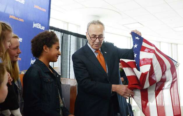Kallie Ahern, 11, of Schuylerville, left, is recognized by Sen. Charles Schumer, right, Monday afternoon, April 6, 2015, at Albany International Airport in Colonie, N.Y., for rescuing a Bald eagle last month. Ahern and her stepfather, Michael Liotta, found the injured bird alongside the road near Schuylerville Central School. She was presented with a flag which was flown over the Capitol in Washington, D.C. (Will Waldron/Times Union) Photo: WW / 00031322A
