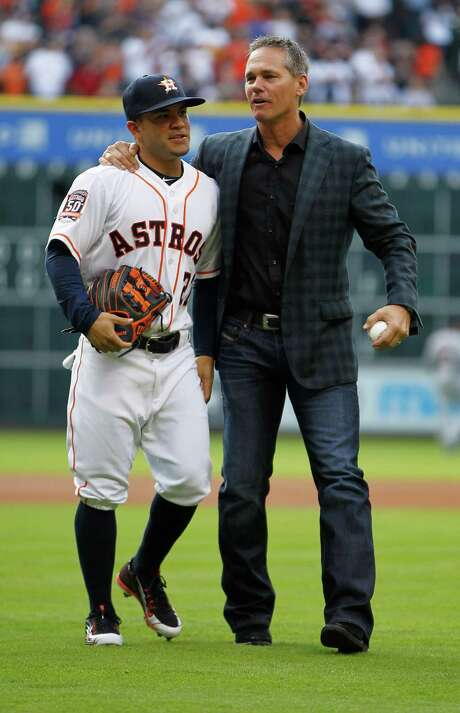 Hall of Famer and former Astro Craig Biggio hugs second baseman Jose Altuve after the ceremonial first pitch Monday at Minute Maid Park. The two talked about sharing the opening-day buzz with teammates. Photo: Karen Warren, Staff / © 2015 Houston Chronicle