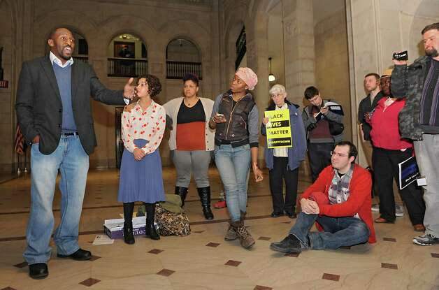 Garry Murray of Albany, left, speaks during a teach-in to learn about how to form a cop watch in the lobby of the Albany City Hall on Monday, April 6, 2015 in Albany, N.Y. The people then walked upstairs to voice their opinion over Donald Ivy's death last week after a police encounter with a Taser in the Common Council chamber. (Lori Van Buren / Times Union) Photo: Lori Van Buren / 00031326A