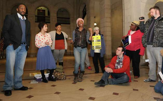 Amani Olugbala of Albany, center, speaks during a teach-in to learn about how to form a cop watch in the lobby of the Albany City Hall on Monday, April 6, 2015 in Albany, N.Y. The people then walked upstairs to voice their opinion over Donald Ivy's death last week after a police encounter with a Taser in the Common Council chamber. (Lori Van Buren / Times Union) Photo: Lori Van Buren / 00031326A