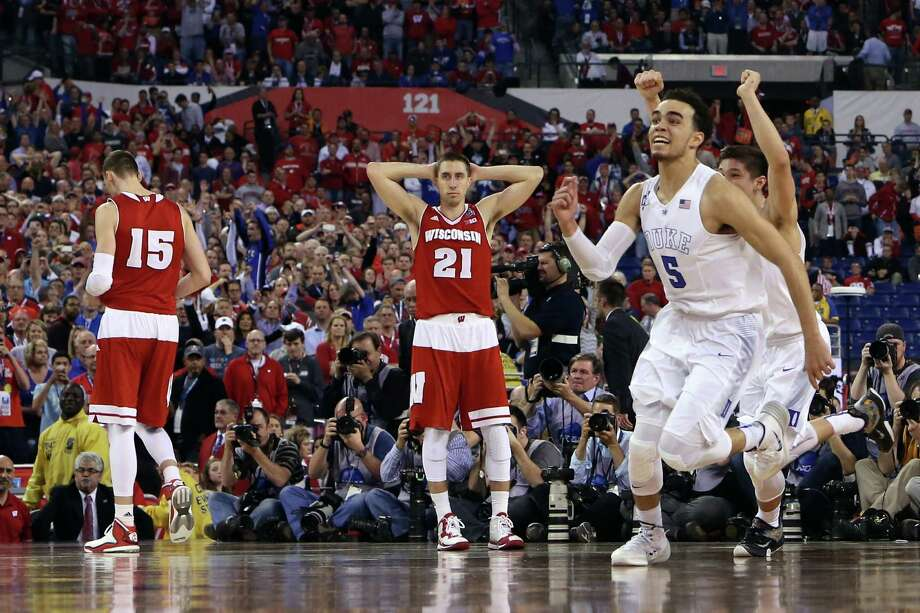Tyus Jones (5) and Grayson Allen (behind Jones) of the Duke Blue Devils celebrate after defeating the Wisconsin Badgers as Sam Dekker (15) and Josh Gasser (21) at Lucas Oil Stadium on April 6, 2015, in Indianapolis. Duke defeated Wisconsin 68-63 in the national title game. Photo: Andy Lyons /Getty Images / 2015 Getty Images