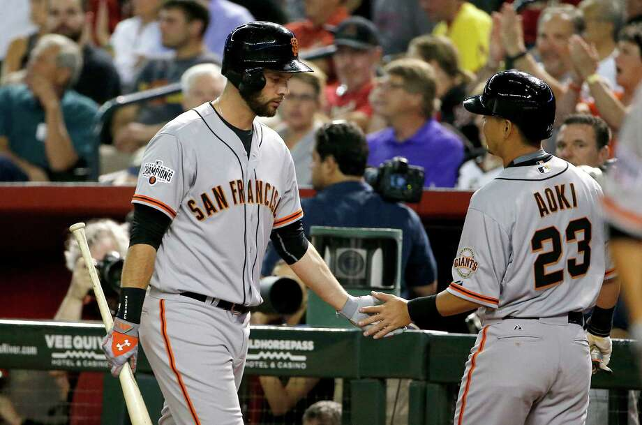 Giants first baseman Brandon Belt (left), greeting Norichika Aoki after Aoki scored a run against Arizona during the fifth inning Monday, will not have to go on the disabled list after suffering a minor groin strain in Tuesday's game. Photo: Ross D. Franklin / Associated Press / AP