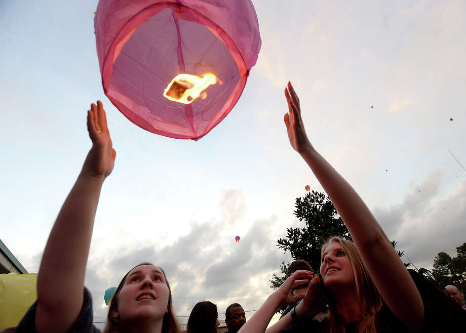 Paige Rucker (left) and Emily Werkheiser watch as their lantern takes flight during the CASA candlelight vigil held Monday outside the Orange County Courthouse. The event, at which 151 lanterns were released to honor the 151 children in Texas who died as a result of abuse and neglect, featured music, poetry, prayer, and child ID's courtesy of the Orange County Sheriff's Department. Photo taken Monday, April 6, 2015 Kim Brent/The Enterprise Photo: Kim Brent / Beaumont Enterprise