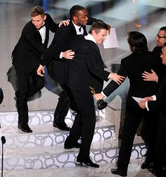 """The cast and crew of  """"The Hurt Locker"""" celebrate as they go on stage to accept the Oscar for best motion picture of the year at the 82nd Academy Awards Sunday, March 7, 2010, in the Hollywood section of Los Angeles. From left are Brian Geraghty,  Anthony Mackie and Jeremy Renner. (AP Photo/Mark J. Terrill) Photo: Mark J. Terrill, AP / AP"""