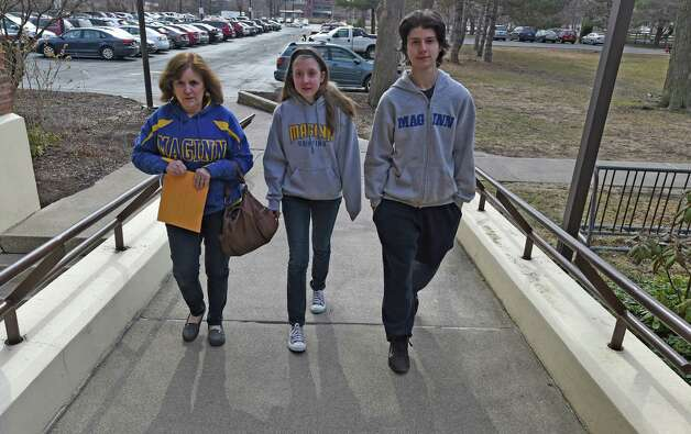 Robin Jira, left, accompanied by her children Juliana, 14, and Matthew, 16, holds letters to be delivered to Albany Bishop Edward Sharfenberger from parents upset by the plan to move students from the Bishop Maginn School to another location Monday April 6, 2015, in Albany, N.Y. (Skip Dickstein/Times Union) Photo: SKIP DICKSTEIN / 00031310A