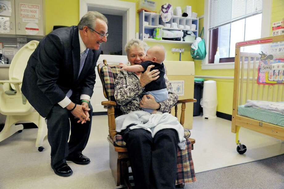 Troy Mayor Lou Rosamilia, left, visits with Mary Gowie and Jason Helmar, 4 months, at CEO's Lansingburgh Family Resource Center as part of the Mayor's Day of Recognition for National Service on Tuesday, April 7, 2015, in Troy, N.Y.  The Mayor toured the center to see CEO's Foster Grandparent Program in action.  Gowie has been working in the program for the past two years.   The Foster Grandparent Program currently serves seven counties throughout New York.  The program pays low-to-moderate income seniors a small stipend for volunteering with children in their local communities.  (Paul Buckowski / Times Union) Photo: PAUL BUCKOWSKI / 00031316A