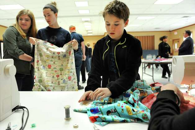 Charlie Mulligan, 10, of Guilderland Center, right, volunteers his time to assist the Train Station Quilters as they sew pillowcases for the Pillowcase Project, which benefits foster children, on Tuesday, April 7, 2015, at the Altamont Village Hall in Altamont, N.Y. (Cindy Schultz / Times Union) Photo: Cindy Schultz / 00031324A