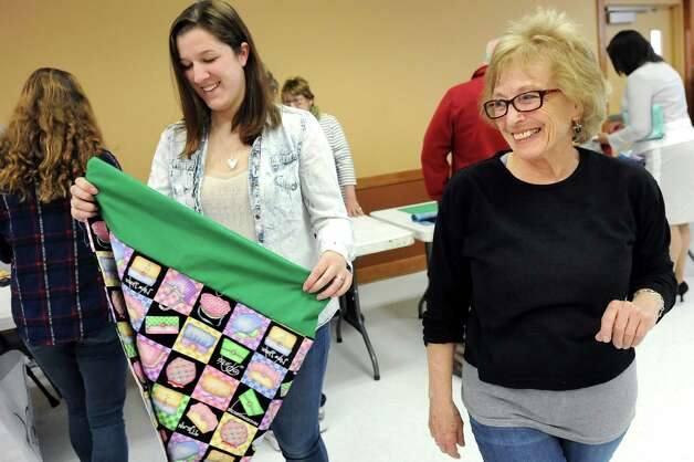 Train Station Quilters organizer Ruth Dickenson, right, gives instructions to volunteer Julia Sanford, 17, center, as they construct pillowcases for the Pillowcase Project, which benefits foster children, on Tuesday, April 7, 2015, at the Altamont Village Hall in Altamont, N.Y. (Cindy Schultz / Times Union) Photo: Cindy Schultz / 00031324A