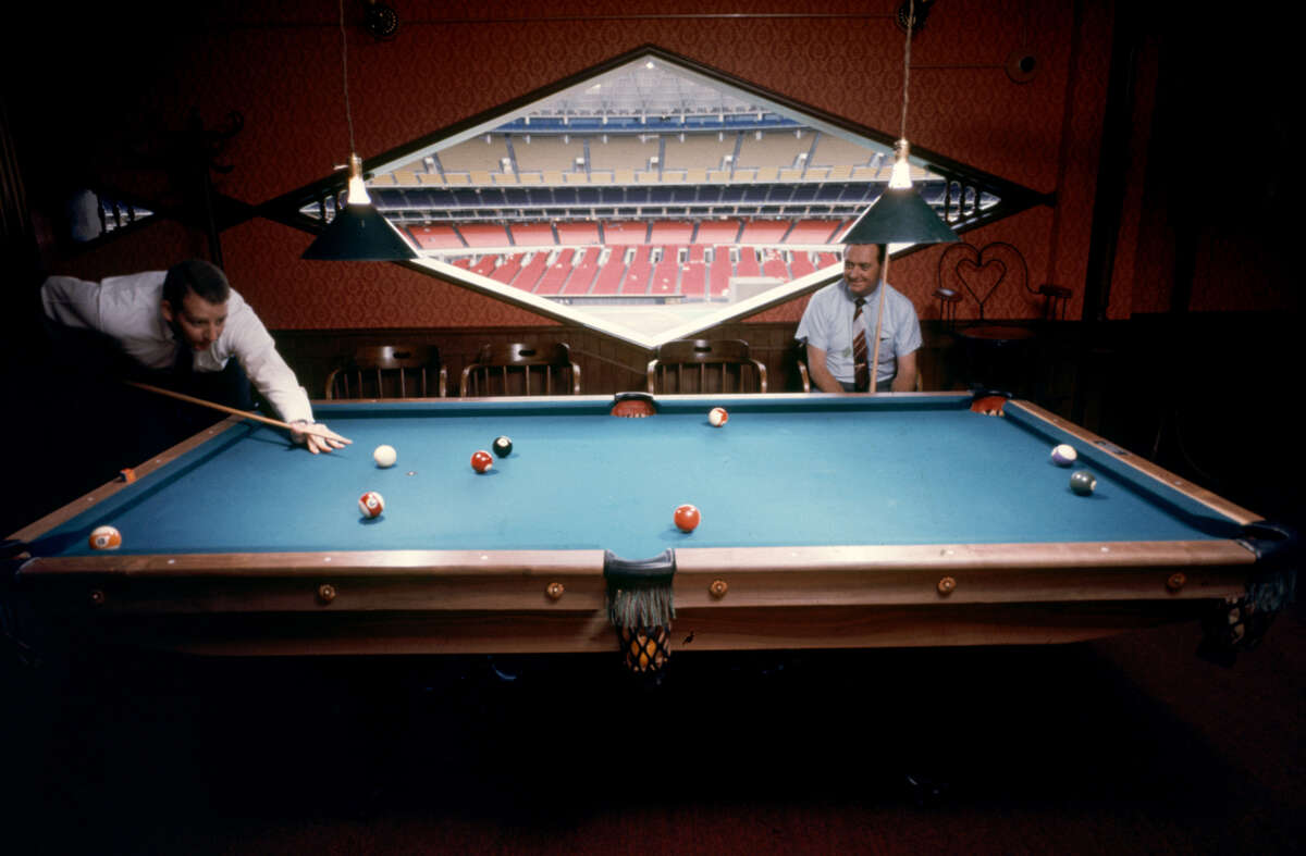 A pair of unidentified men as they play billiards in one of the private 'sky rooms' in the Astrodome, Houston, Texas, June 1968. The field and grandstands are visible though the diamand-shaped window at center.