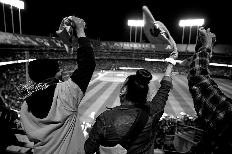 Lavonna Simmons (center) and Mondo Barnes II (left) wave rally towels as the Oakland A's score a 4th inning run on a single by Marcus Semien during 8-0 win over the Texas Rangers in season opener at O.co Coliseum in Oakland, Calif., on Monday, April 6, 2015. Photo: Scott Strazzante / The Chronicle / ONLINE_YES