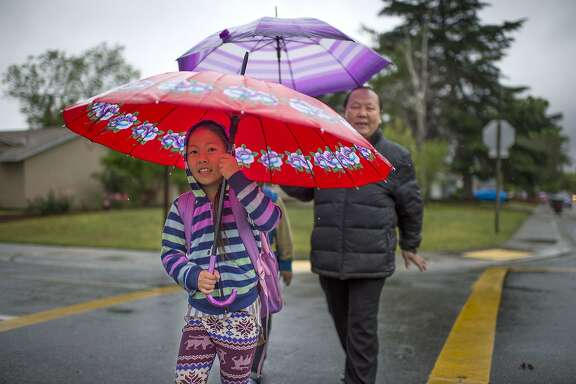 Cecilia Xiong, left, and her father, Kachang Xiong, walk to Parkway Elementary School, Tuesday, April 7, 2015, in Sacramento, Calif. An unusually cold spring storm brought heavy rain and hail to parts of Northern California on Tuesday and coated the mountains in snow.