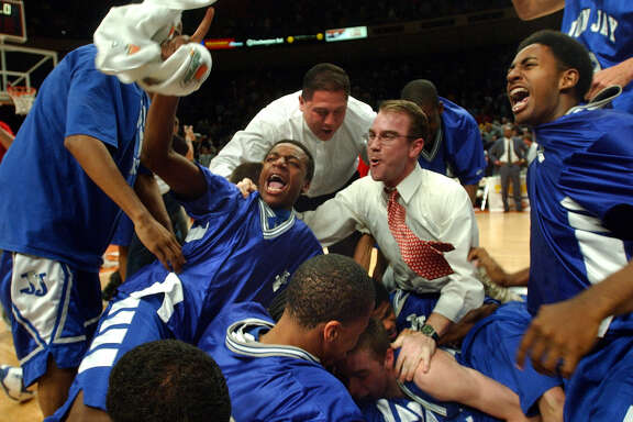 Players and coaches storm the court to celebrate the Jay Mustangs' victory in the Class 5A state championship game on March 9, 2002, at the Erwin Center in Austin.