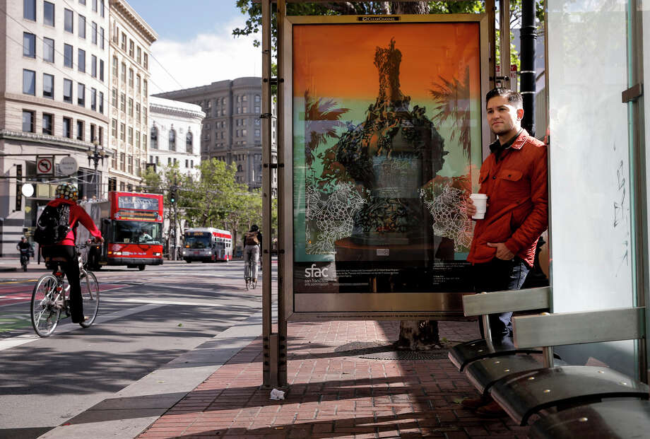 "Robert Minervini stands at a bus stop displaying his artwork ""Le Poème de la Vigne (With Wine Grapes)."" Photo: Michael Macor / The Chronicle / ONLINE_YES"